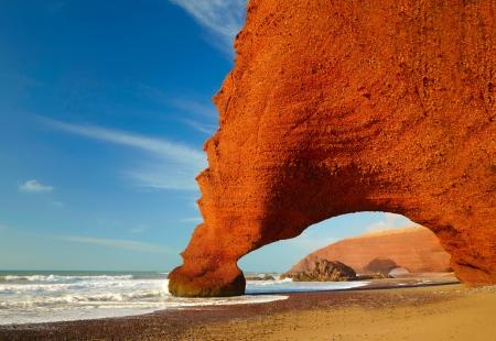 Red archs on atlantic ocean coast. Marocco