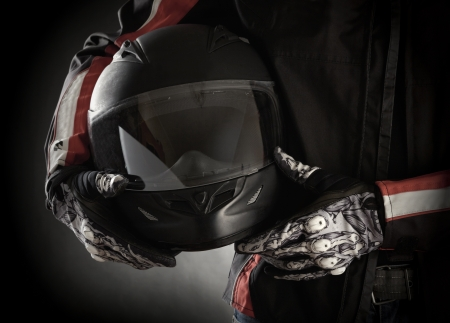 Photo for Motorcyclist with helmet in his hands. Dark background - Royalty Free Image