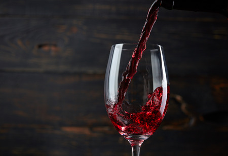 Photo pour Pouring red wine into the glass against dark wooden background - image libre de droit