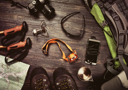 Photo pour Hiking accessories set on dark wooden background:  boots, backpack, sunglasses, photo camera, map, smartphone, flashlight and others. Top view. Vintage retro effect - image libre de droit