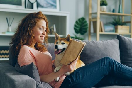 Foto de Pretty student young woman is reading book in cozy apartment smiling and petting adorable dog sitting on comfy couch at home. Animals and hobby concept. - Imagen libre de derechos