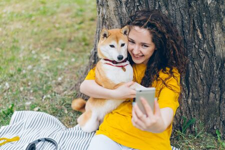 Photo pour Portrait of happy young girl taking selfie with adorable dog in park hugging lovely pet holding camera smiling enjoying friendship with puppy. Youth and lifestyle concept. - image libre de droit