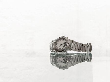 Foto de Used wristwatch in brushed steel with reflection on white background - Imagen libre de derechos