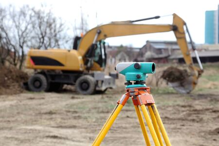 Theodolite on tripod with buldozer in background