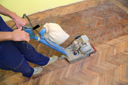 Worker polishing old parquet floor with grinding machine