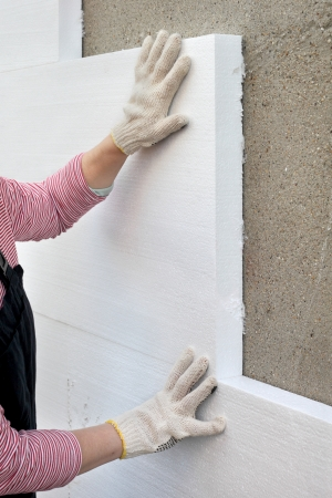 Worker placing polystyrene sheet insulation to the wall