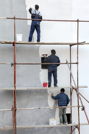 Photo pour Workers at scaffolding spreading stucco over mortar and wall insulation with trowel - image libre de droit