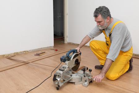 Worker cut wooden batten for laminate floor,  floating wood tile