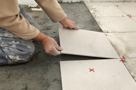 Photo pour Home renovation, worker placing tiles to floor, using cement mixed with sand - image libre de droit
