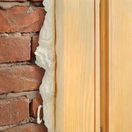 Photo pour Wooden door or window install, closeup of polyurethane foam wood and bricks - image libre de droit