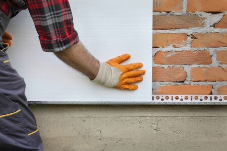 Photo for Worker placing foam, polystyrene thermal insulation to brick wall, house renovation - Royalty Free Image