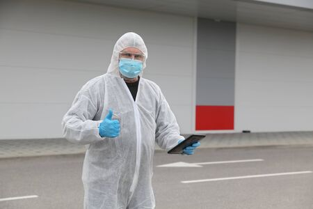 Adult person, worker protected with cloth, surgical mask and gloves gesturing with thumb up and holding tablet, corona virus protection