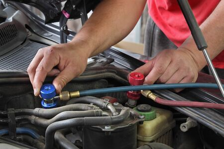 Photo for Mechanic charging air condition unit at modern car, closeup of workers hands and equipment conected to car engine, red and blue clucth couplings - Royalty Free Image