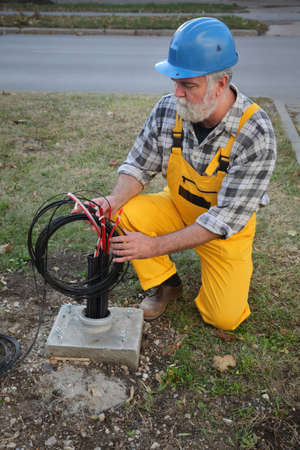 Photo pour Worker installing optic fiber cables for internet and telephone, power lines installation at street - image libre de droit