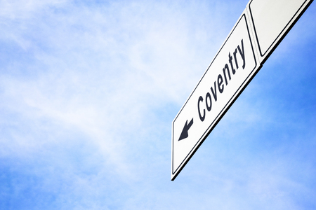 White signboard with an arrow pointing left towards Coventry, England, United Kingdom, against a hazy blue sky in a concept of travel, navigation and direction