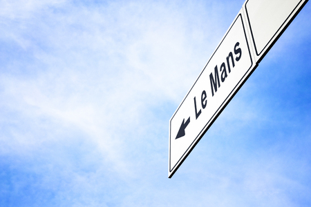 White signboard with an arrow pointing left towards Le Mans, France, against a hazy blue sky in a concept of travel, navigation and direction. Path included for the signboard