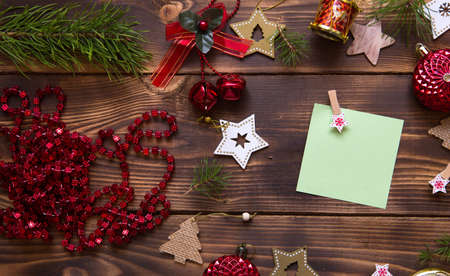 Photo for Christmas flat lay of red balloons and wooden stars and clothespins on a dark background with a square sheet for notes in the center. New year's frame, space for text. Xmas toys, beads, pine branches - Royalty Free Image