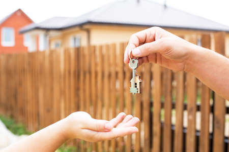 Photo pour Hand with a key and a wooden key ring-house. Background of fence and cottage. Building, project, moving to a new home, mortgage, rent and purchase real estate. To open the door. Copy space - image libre de droit