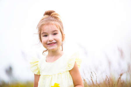 Photo for Portrait of a cute girl in field with a wild flower. Childhood, holidays in the country, freedom and carelessness. Summer time. International Children Day. Mosquito repellent, cottage core. Copy space - Royalty Free Image