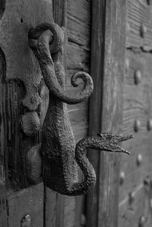 Original metal knocker on an old wooden door in black and white