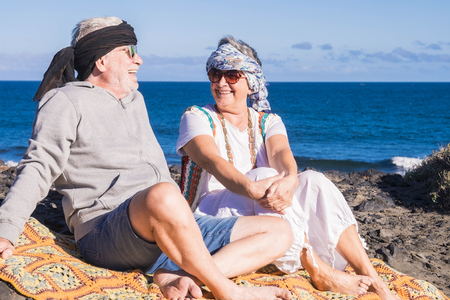 happy couple of senior people gentleman and lady sit down near the ocean with hippy colored clothes style. enjoy and have fun with alternative lifestyle