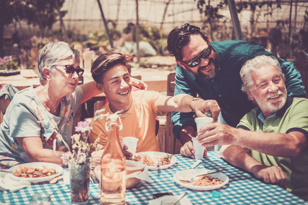 group of beautiful caucasian family from grandfathers to father and grandson having fun celebrating and eating together in an alternative outdoor natural restaurant for a healthy lifestyle. italian pasta food and happiness concept