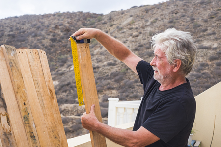 Adult retired man work outdoor like carpenter taking measure dimensions of wooden table - building and reparing or restoring in leisure activiy time - silver society lifestyle