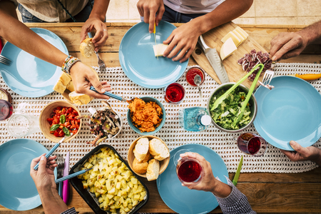 Photo pour People eating together in friendship or family celebration with table full of food viewed from vertical top - friends and have fun concept - colors and background with wooden table - image libre de droit