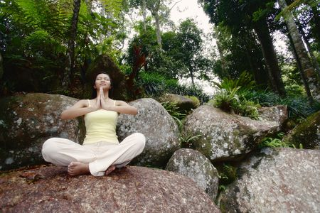 Young Asian Female Sitting on a Rock and Meditating