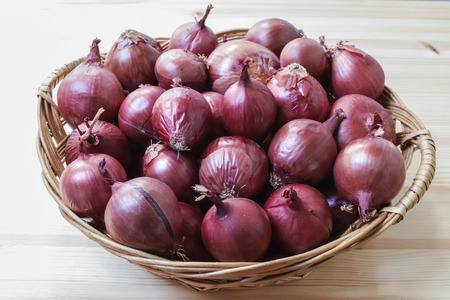 Group of red onions in a wicker basket. Horizontal composition.の写真素材