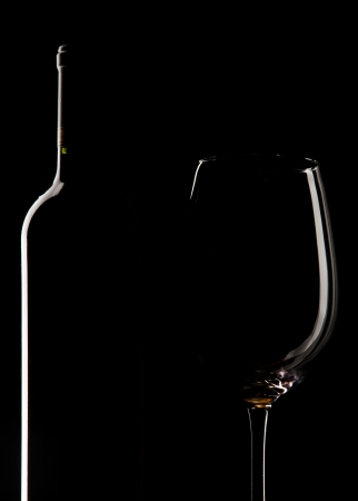 Elegant wine bottle and wine glass, cup, in a black background