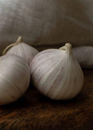 Foto für Three solo garlic on wooden table textile background close-up - Lizenzfreies Bild