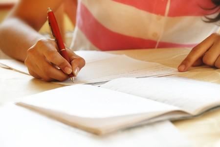 schoolgirl with pen writing down in notebook homework