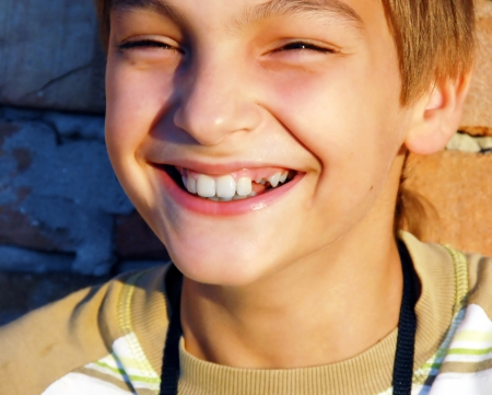 laughing teen caucasian boy with missing tooth portrait
