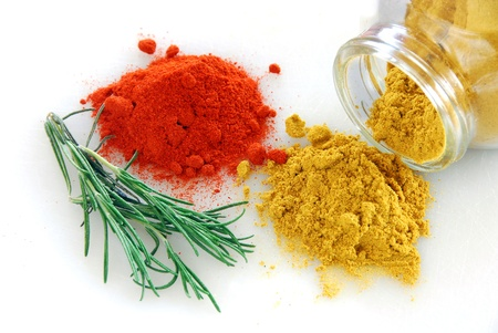 red paprika and curry heaps with rosemary branch on white background