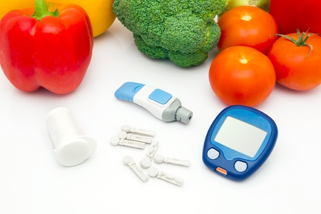 Glucose meter device with accessories. Vegetables and healthy lifestyle