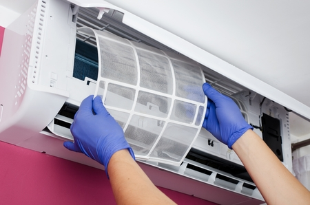 Photo pour Air conditioner cleaning. Man in gloves checks the filter. - image libre de droit