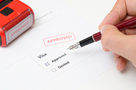 Visa and approved stamp on a document form. Immigration and travel concept