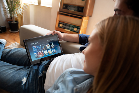 Photo pour Couple using digital tablet for watching movie on VOD service. Video On Demand television internet stream multimedia concept - image libre de droit