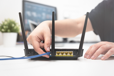 Photo pour Man connects the internet cable to the router's socket. Fast and wireless internet concept - image libre de droit