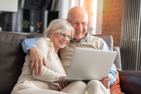 Photo for Senior couple browsing the internet together. Retirees using a laptop computer at home - Royalty Free Image