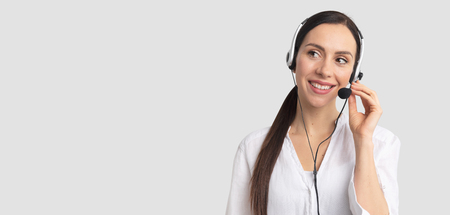 Photo pour Consultant of call center in headphones on gray background. Helpline operator with headset - image libre de droit