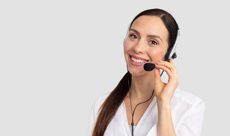 Photo for Consultant of call center in headphones on gray background. Helpline operator with headset - Royalty Free Image