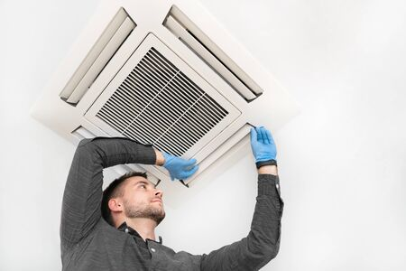 Photo for Handsome young technician repairing air conditioner. Installing air conditioning system. - Royalty Free Image