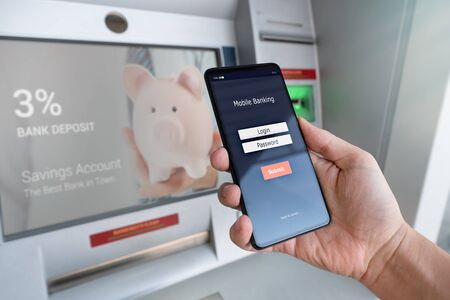 Photo pour Withdraw money from an ATM without using a credit card. Person holding a phone with a login screen for mobile banking. - image libre de droit