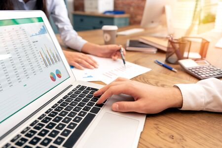 Photo for Investors work in the office. Financial advisor with laptop and graph on the screen. Woman pointing on statement - Royalty Free Image