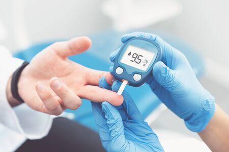Foto de Doctor checking blood sugar level with glucometer. Treatment of diabetes concept. - Imagen libre de derechos