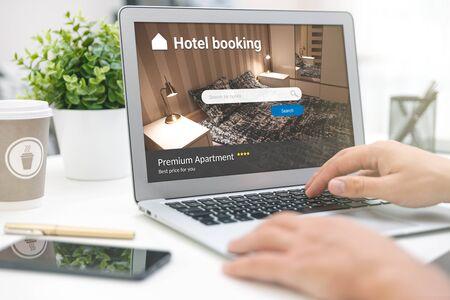 Photo pour Man makes hotel reservations via the internet. Tourism, vacation concept - image libre de droit