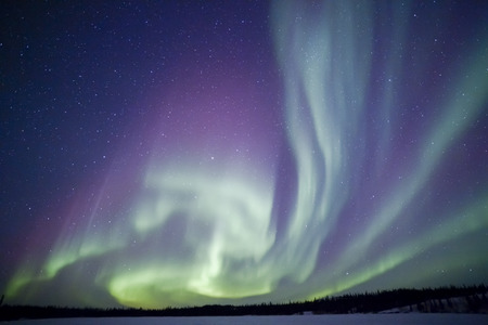 Northern lights aurora borealis in the night sky over beautiful frozen lake landscape