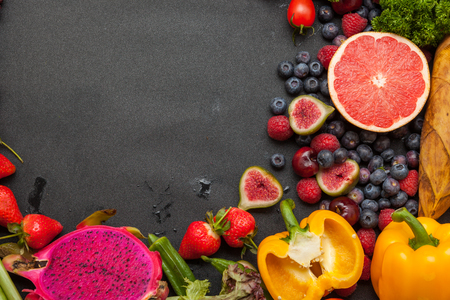 Foto de Vegetables and fruits, on the black background board - Imagen libre de derechos